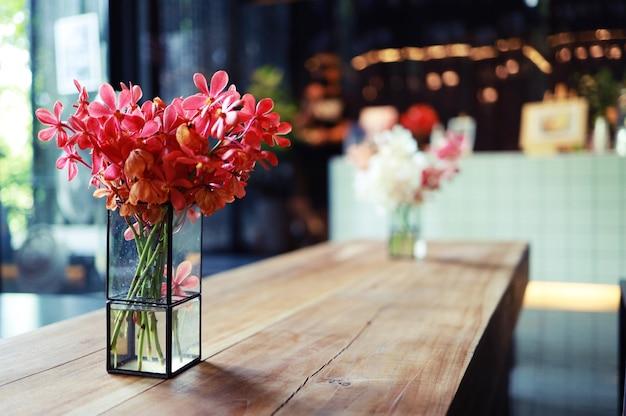 Roze bloem in vaas staat op tafel in een café