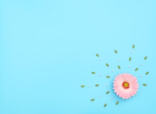 Roze bloem met groene bladeren en parels op blauwe achtergrond