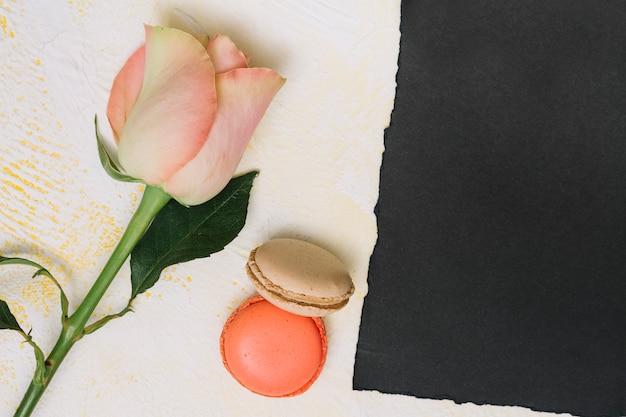 Roze bloem met koekjes en zwart papier op tafel