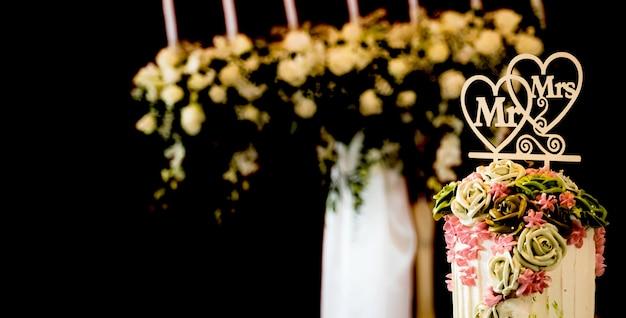 Roze bloem op de bruidstaart voor het bruid en bruidegom paar gesneden in het huwelijksfeest in een restaurant of kerk.