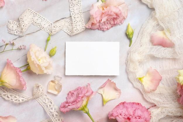 Roze bloemen en een blanco wenskaart op een marmeren tafel