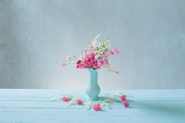 Roze bloemen in blauwe vaas op blauwe achtergrond