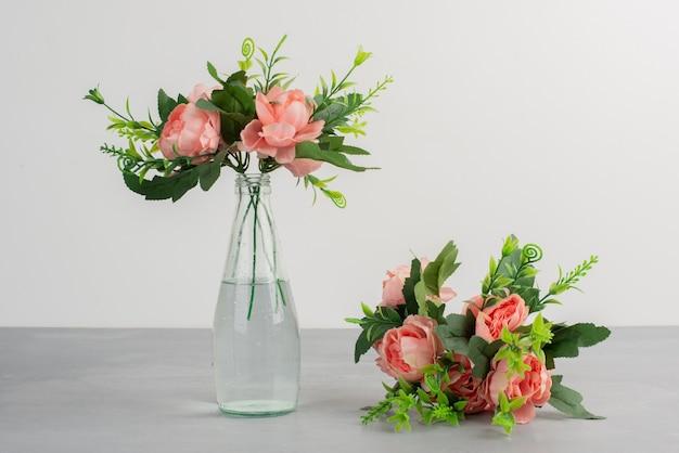 Roze bloemen in een glazen vaas en een boeket bloemen op grijze tafel