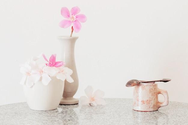 Roze bloemen in een vaas en kopje koffie