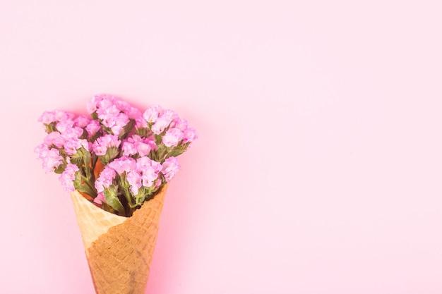 Roze bloemen in een wafelkegel voor roomijs op een roze achtergrond.