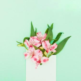 Roze bloemen in envelop op tafel
