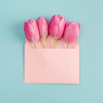 Roze bloemen in papieren envelop
