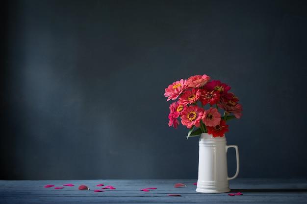 Roze bloemen in witte kruik op donkerblauwe achtergrond