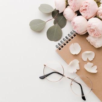 Roze bloemen met bladerenregeling met glazen hoge mening