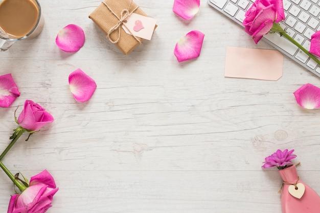 Roze bloemen met geschenkdoos en toetsenbord op tafel