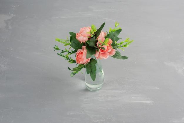 Roze bloemen met groene bladeren in een glazen vaas.