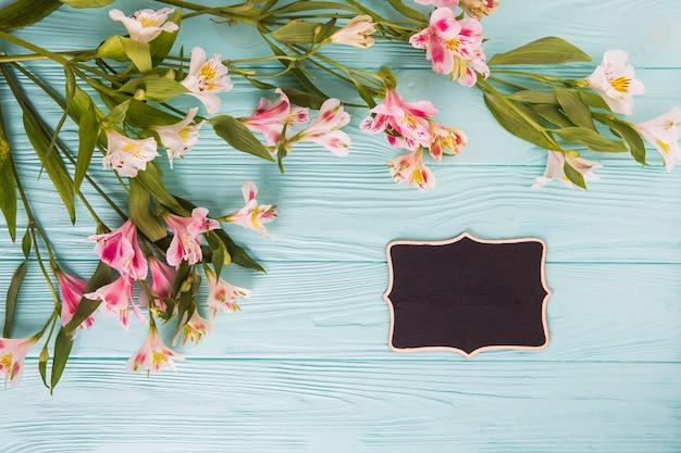 Roze bloemen met kleine schoolbord op tafel