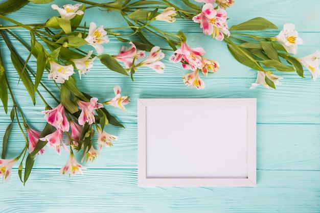 Roze bloemen met leeg frame op tafel