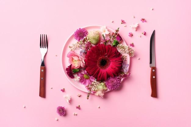 Roze bloemen op roze plaat, vork, mes over pittige pastel achtergrond.