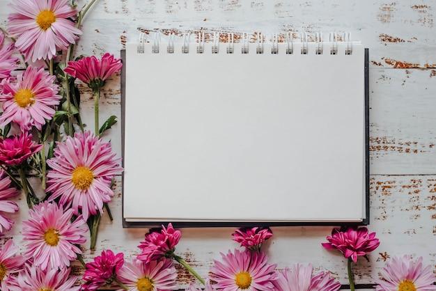 Roze bloemenlijst, witte houten achtergrond met kopie van de ruimte