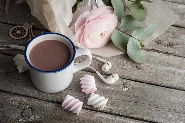 Roze boterbloem, koptelefoons, warme chocolademelk