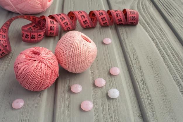 Roze breiwerk en roze centimeter op de grijze houten ondergrond