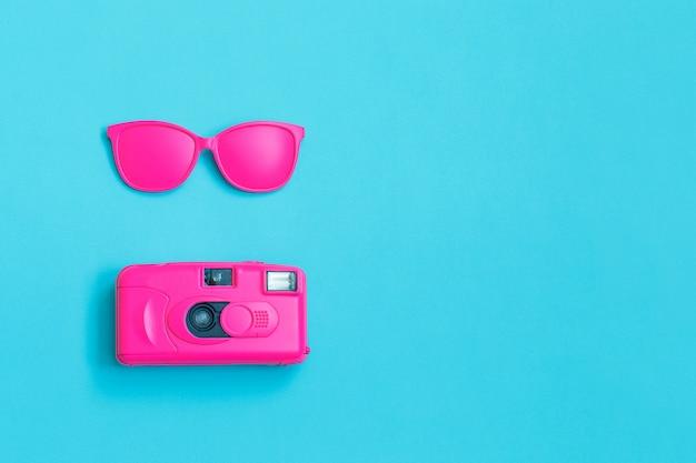Roze bril en roze camera op blauw