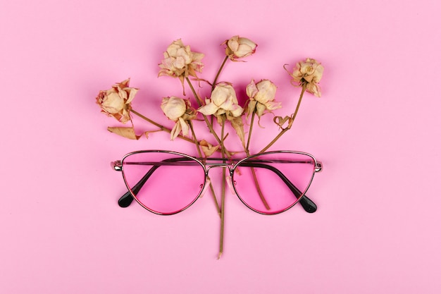 Roze bril in kleuren. plat lag. glamour en stijl. brillen voor dames. roze bril op een roze achtergrond versierd met gedroogde rozen.