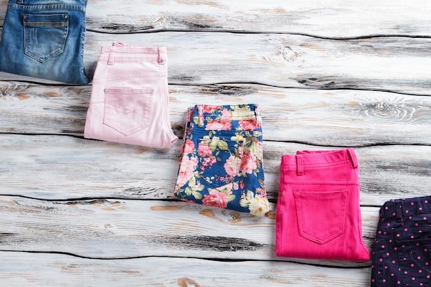 Roze broek en spijkerbroek. gevouwen denim broek. nieuwe kleding op houten vloer. exclusieve items uit de voorjaarscollectie.