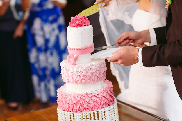 Roze bruidstaart. bruid en bruidegom staan in de buurt van een bruidstaart.