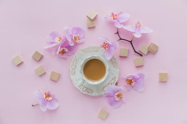 Roze cadeauzakje en vliegende orchideebloemen op lichtroze oppervlak. bovenaanzicht wenskaart met delicate bloemen, kopje koffie en lege houten blokken. vrouwendag, moederdag groet concept.