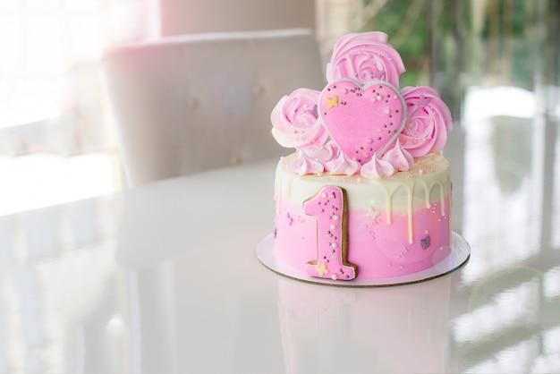 Roze cake bij de viering van de eerste verjaardag van het meisje