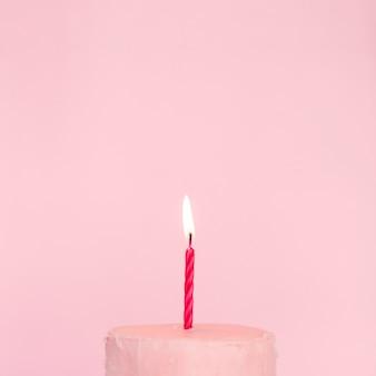 Roze cake met aangestoken kaars