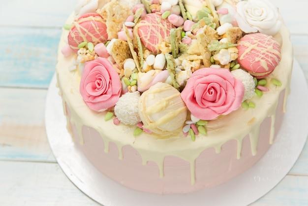 Roze cake met bloemen en cakejes op een witte plaat