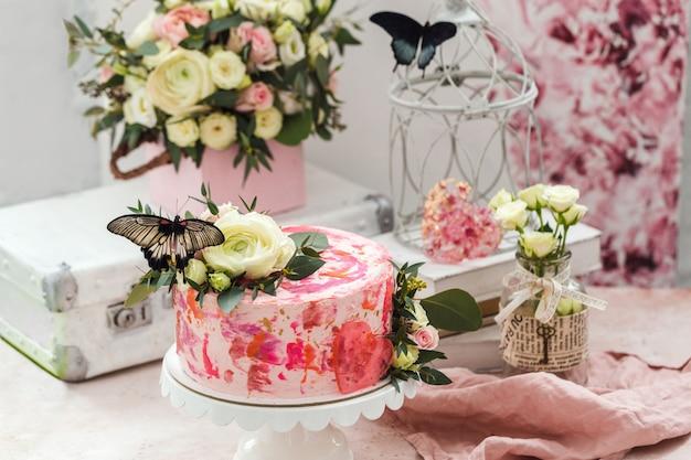 Roze cake versierd met bloemen en echte vlinders steeg romantische sfeer