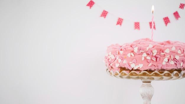 Roze cake versierd met kaars