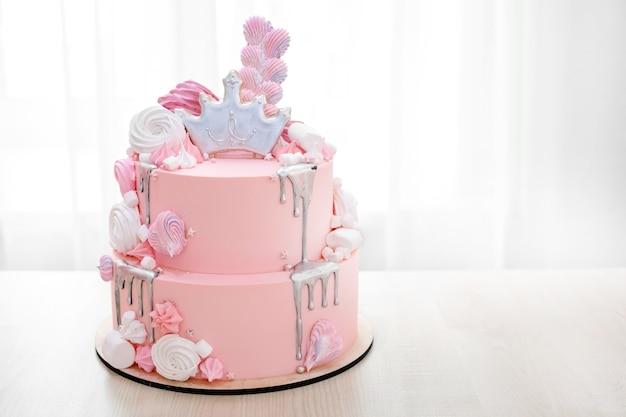 Roze cake versierd met kroon van prinses