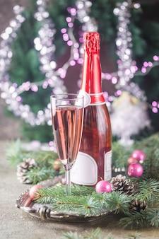 Roze champagne in een glas en kerstversiering