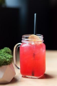 Roze cocktail met citroen en zwart stro, koud drankje in café.