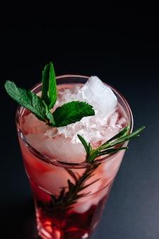 Roze cocktail met munt en rozemarijn close-up bovenaanzicht