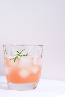Roze cocktail met rozemarijn en ijs in glas op een wit tafelkleed op de lijst