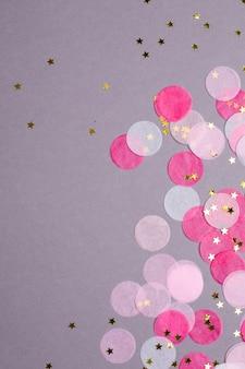 Roze confetti met gouden sterren op grijs met copyspace