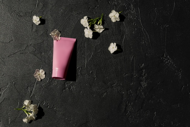 Roze cosmetische tube met gezichtscrème, bodylotion of reinigingsmiddel op een donkere achtergrond met bloeiende witte bloemen. gevoelig huidverzorgingsconcept. kopieer de ruimte, bespotten.