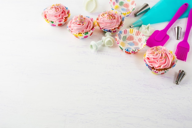 Roze cupcakes en kookgerei uitnodigingsachtergrond