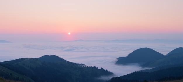 Roze dageraad boven de wolken in de bergen