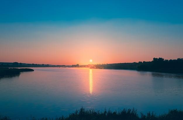 Roze dageraad de zon komt op boven het blauwe kalme water van de vijver een strook zonlicht wordt weerspiegeld in de...