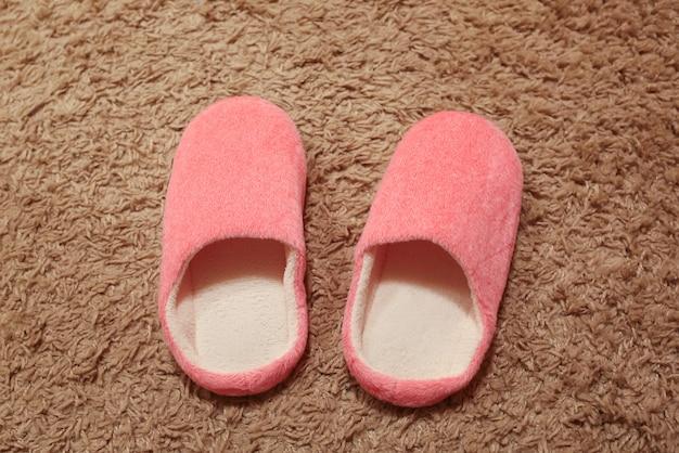 Roze damespantoffels die zich op het tapijt bevinden. huis schoenen.