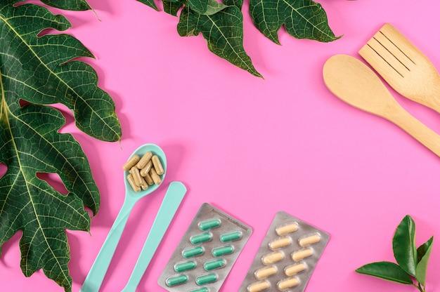 Roze decoratie als achtergrond met voedingssupplementen met materiaal en groen blad. lepel en voedingssupplementen geneeskunde geïsoleerd op roze achtergrond.
