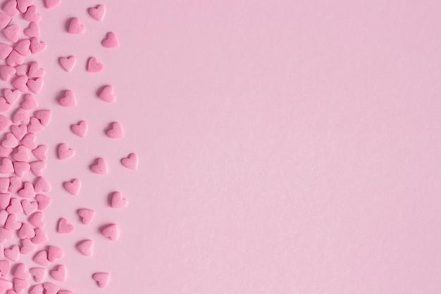 Roze die banketbakkerijharten aan linkerkant op roze achtergrond worden gevestigd, exemplaarruimte
