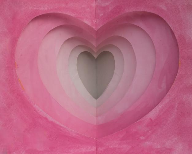 Roze die waterverfkaart van document in hartvorm wordt gesneden in vele lagen voor achtergrond of deco