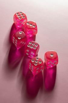 Roze dobbelstenen op roze achtergrond