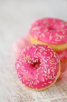 Roze donut. drie roze donuts op een houten licht