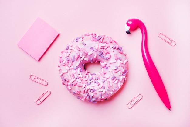 Roze donut en flamingo pen op een roze achtergrond. bovenaanzicht plat leggen.