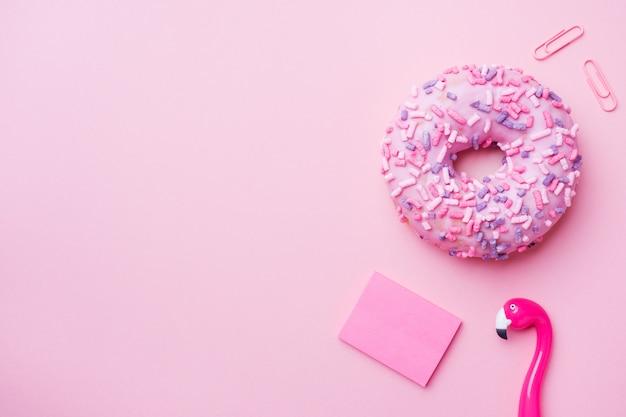 Roze donut en flamingo pen op roze. bovenaanzicht plat leggen.