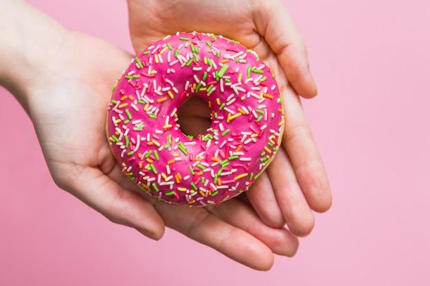 Roze donut in handen op roze achtergrond. vrouw met roze donut